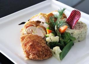 Куриная грудка, фаршированная пармезаном, которая подается с сезонными овощами, картофельным пюре с трюфелями и соусом